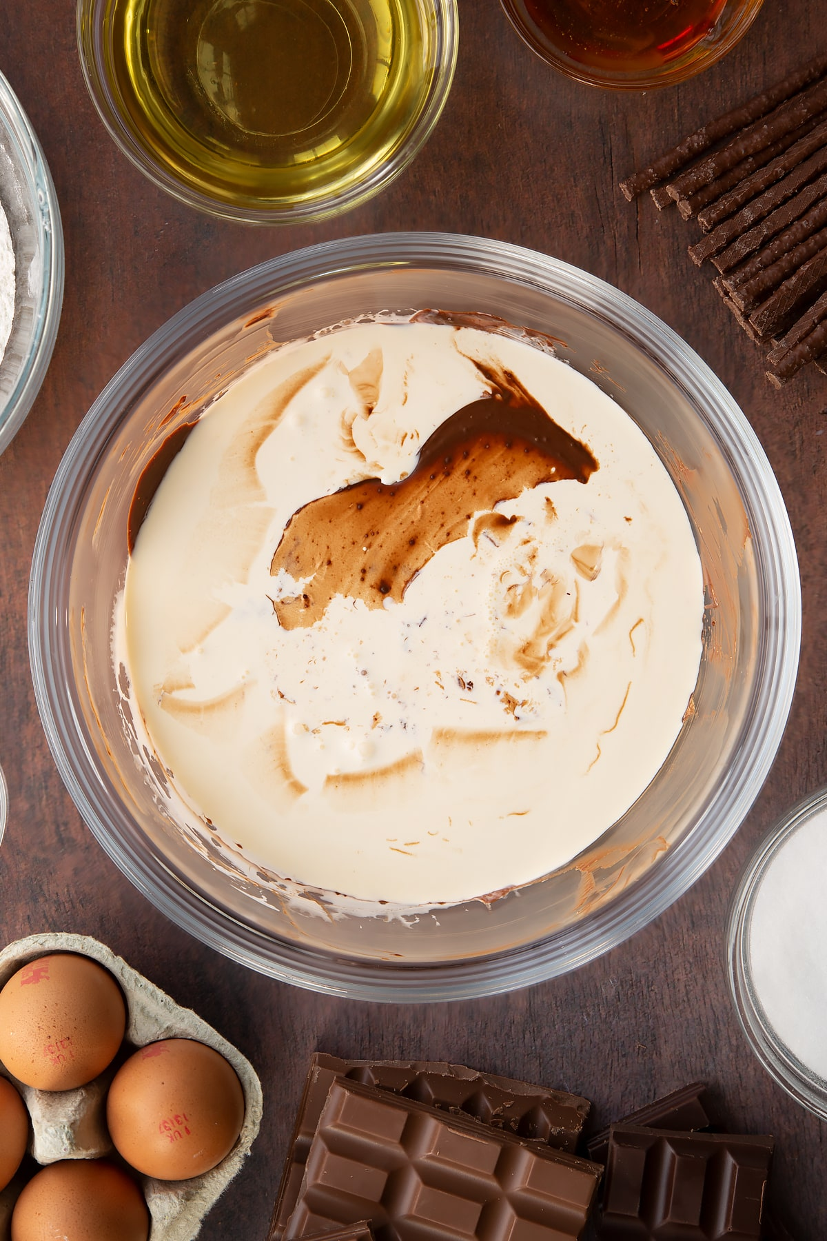 Melted dark chocolate, milk chocolate and Matchmakers in a glass mixing bowl with cream on top. Ingredients to make Matchmaker cake surround the bowl.