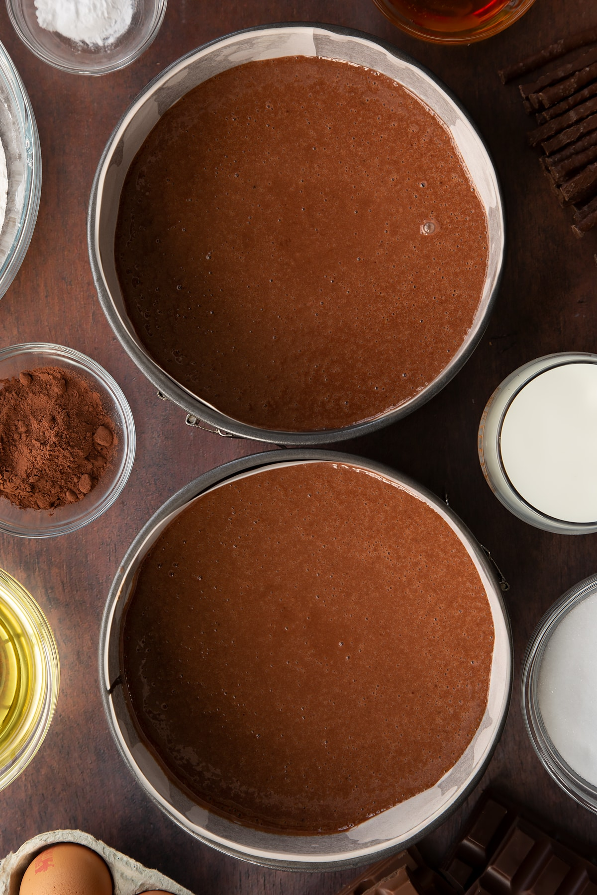 Chocolate cake batter in a two lined baking tins. Ingredients to make Matchmaker cake surround the tins.