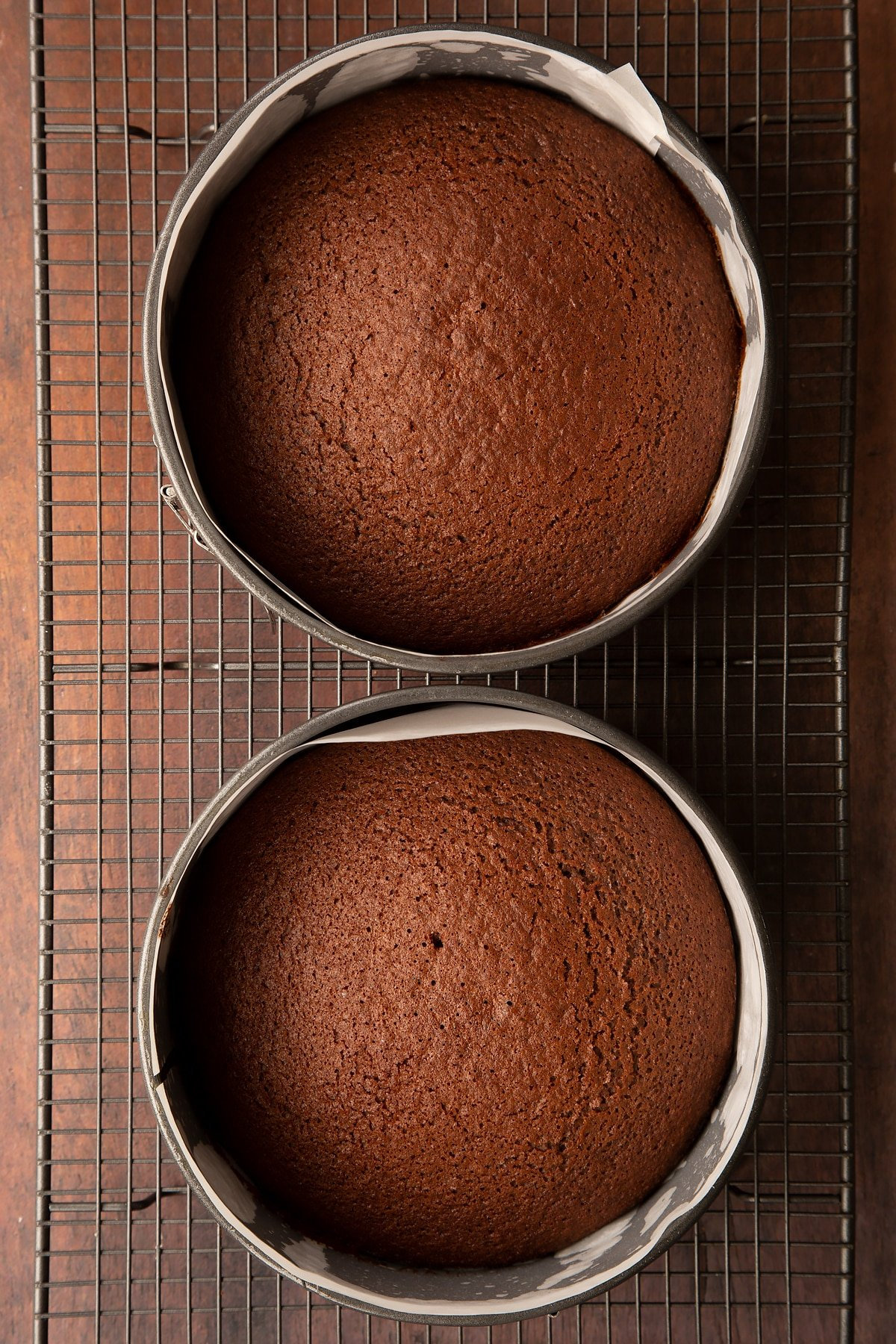 Chocolate cakes in a two lined baking tins on a wire rack.