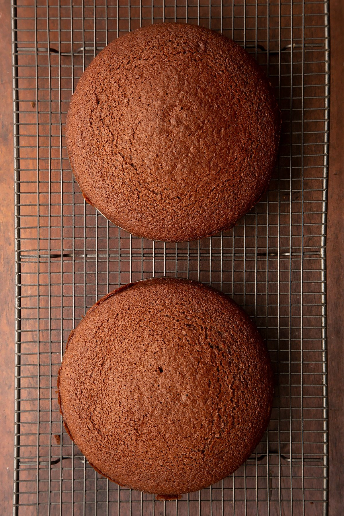 Two chocolate cakes on a wire rack.
