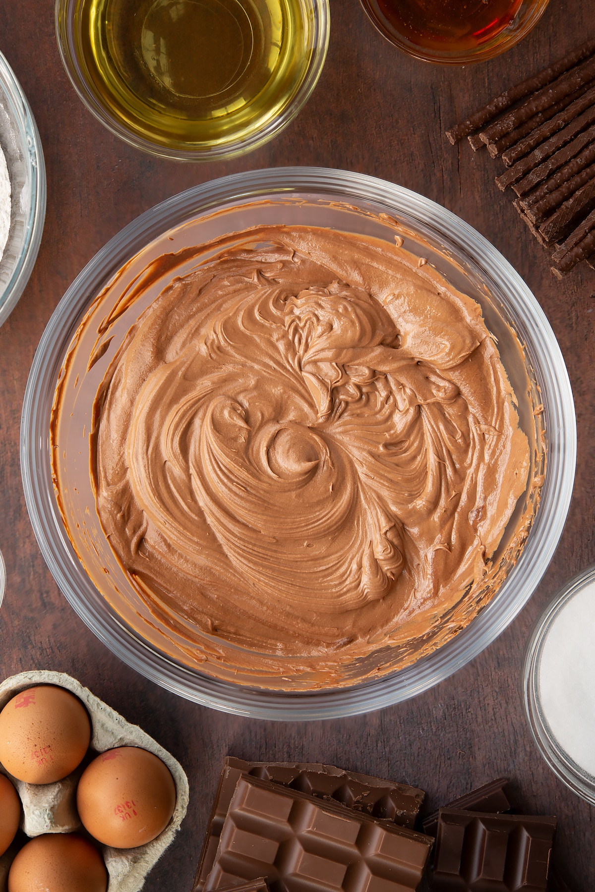 Whipped Matchmaker ganache in a glass mixing bowl. Ingredients to make Matchmaker cake surround the bowl.