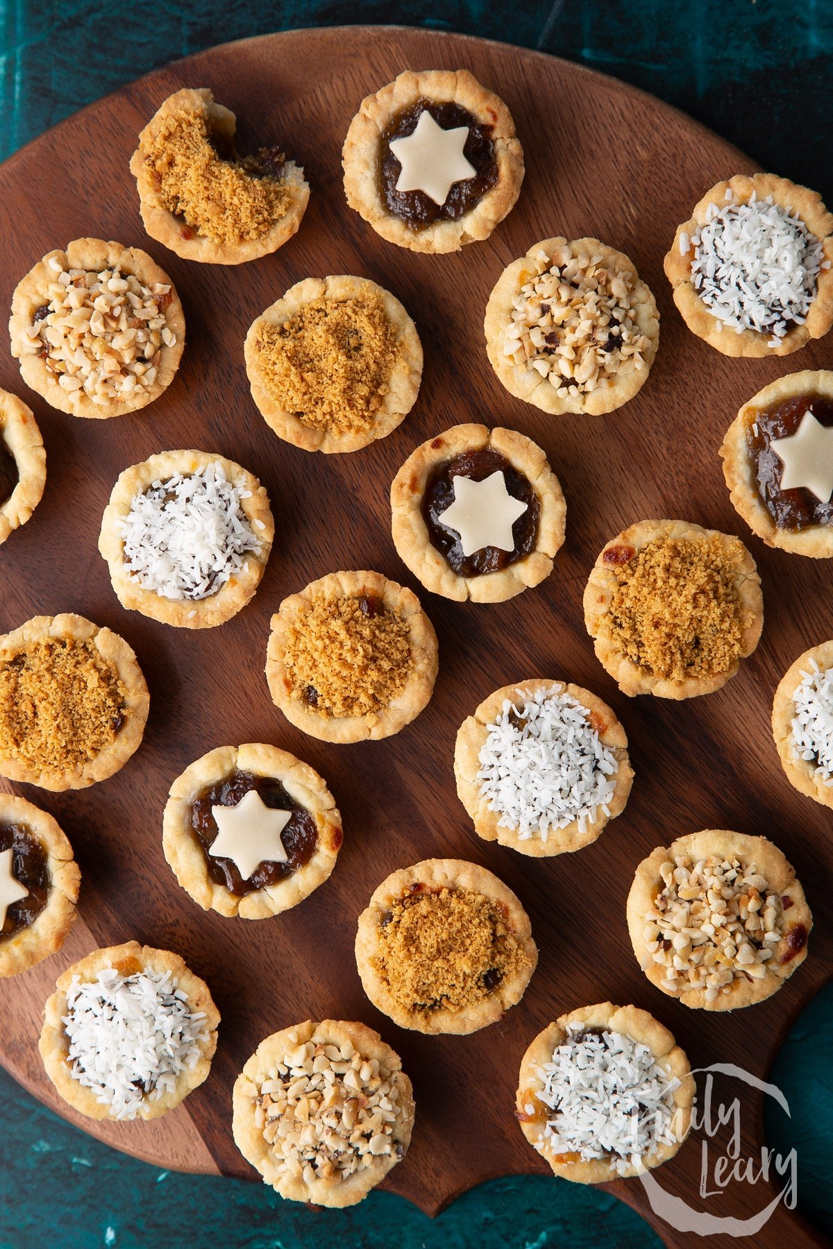 Mini mince pies, shown from above on a dark wooden board.