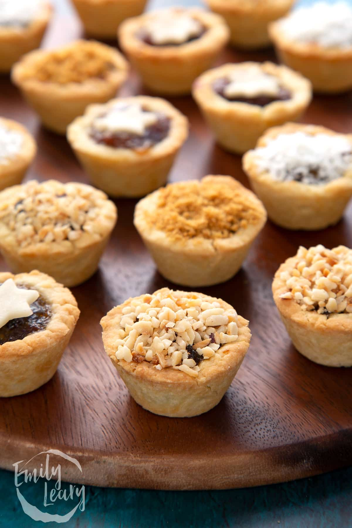 A chopped hazelnut topped mini mince pie. More mini mince pies are also on the dark wooden board.
