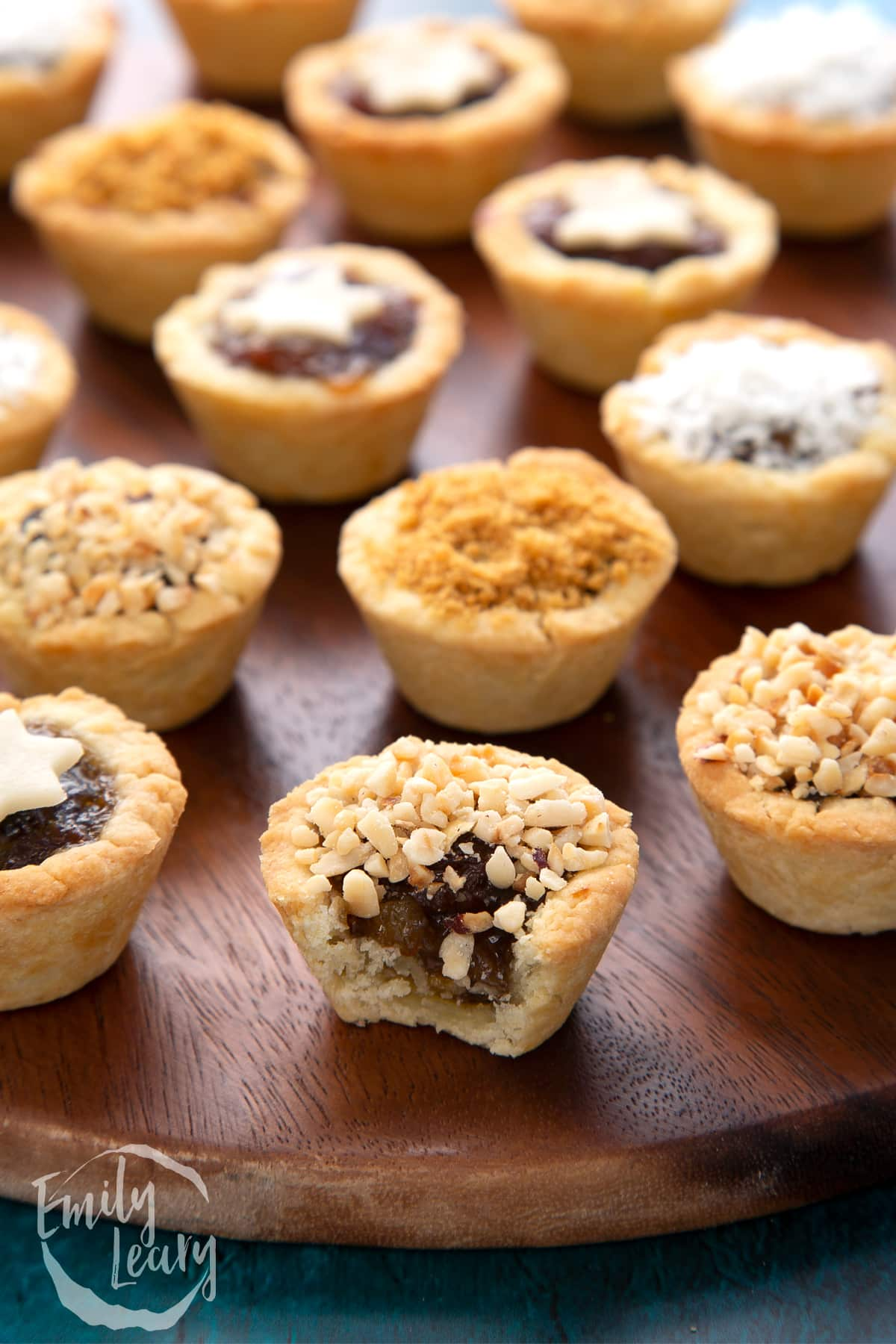 A chopped hazelnut topped mini mince pie with a bite out of it. More mini mince pies are also on the dark wooden board.