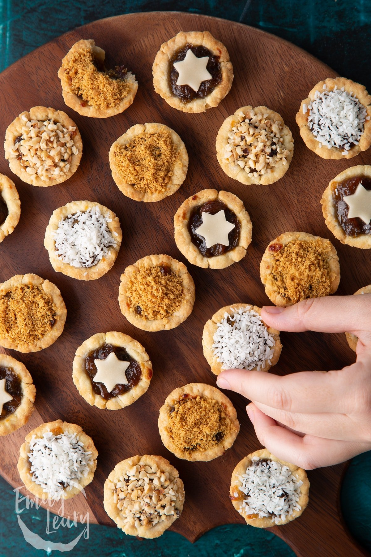 Mini mince pies, shown from above on a dark wooden board. A hand reaches for a desiccated coconut topped one.