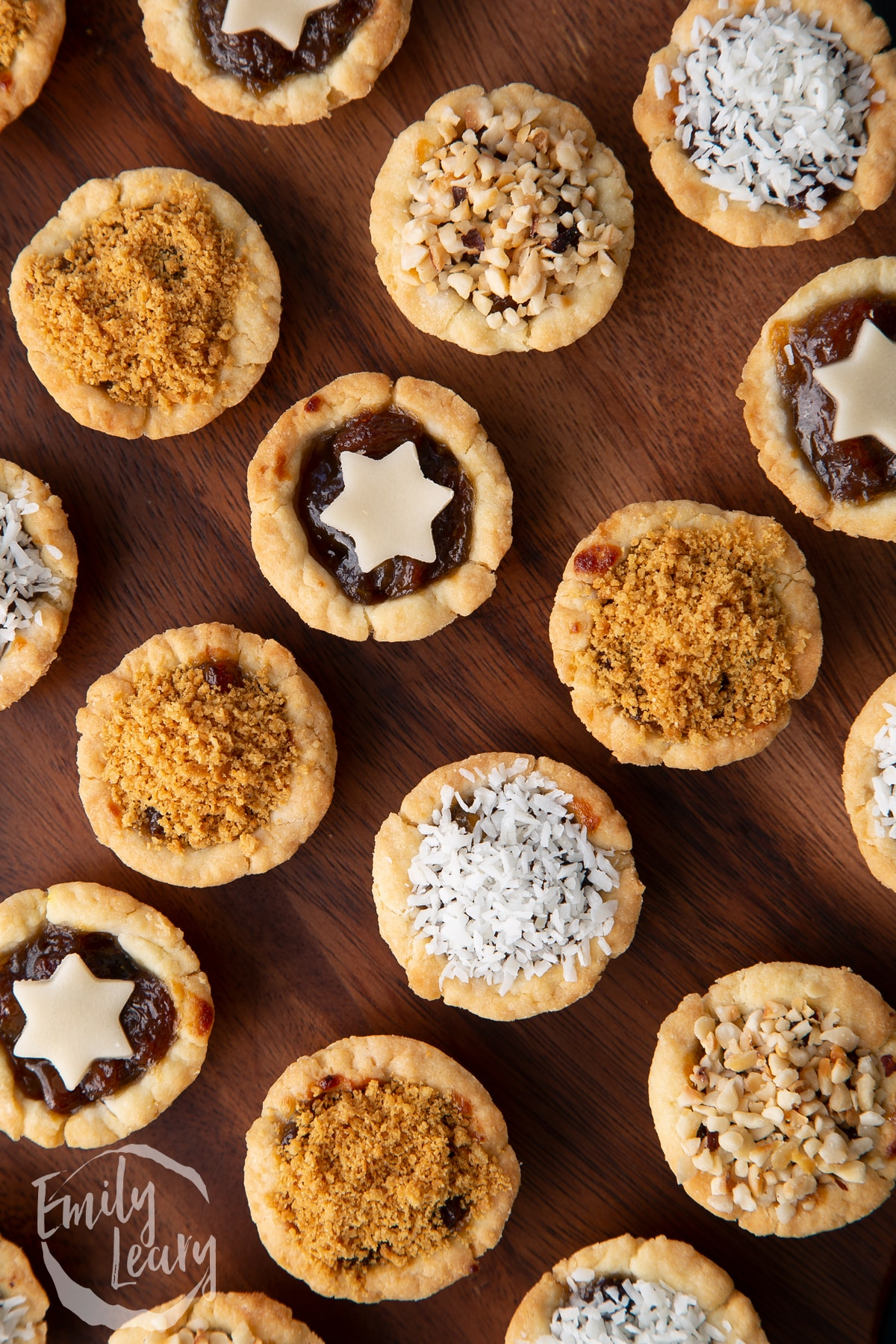 Close up on mini mince pies, shown from above on a dark wooden board.