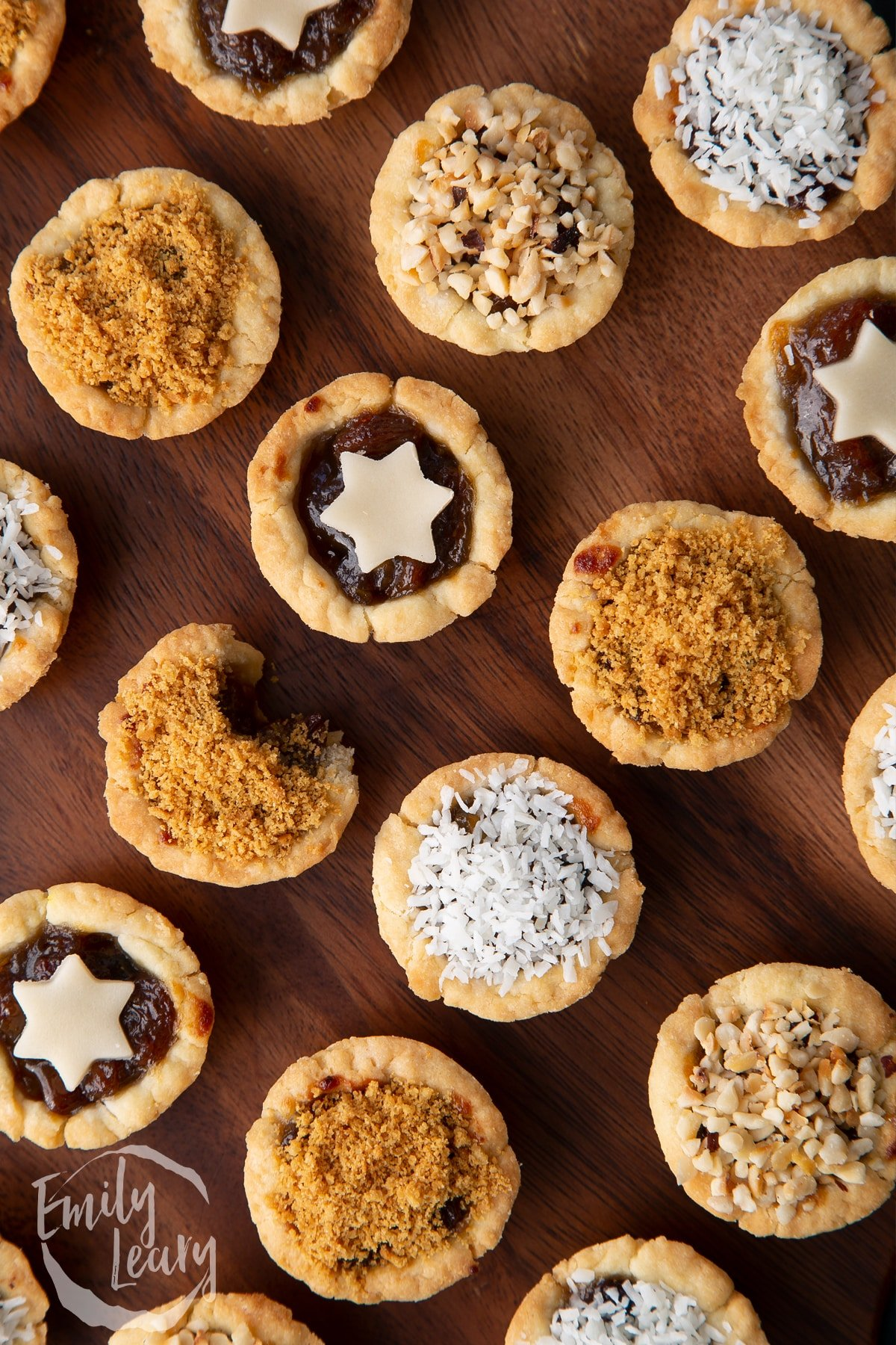 Close up on mini mince pies, shown from above on a dark wooden board. One has a bite out of it.