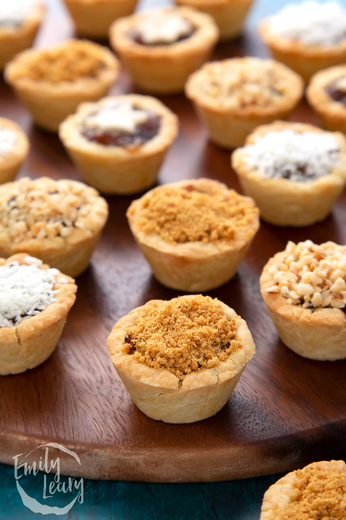 A crushed gingernut topped mini mince pie, with more mini mince pies on a dark wooden board.