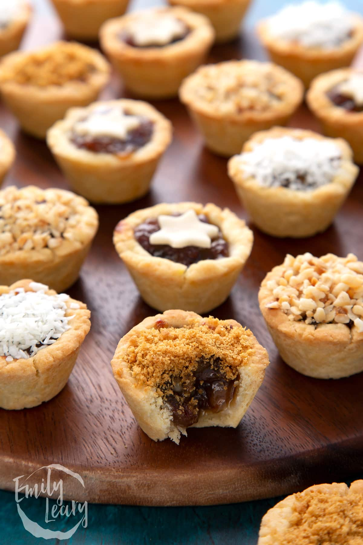 A crushed gingernut topped mini mince pie with a bite out of it. More mini mince pies are also on the dark wooden board.