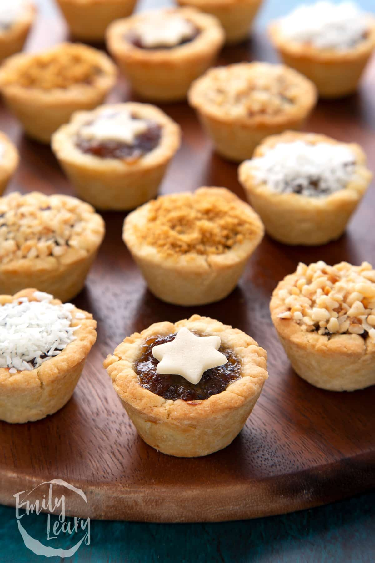 A marzipan star topped mini mince pie. More mini mince pies are also on the dark wooden board.