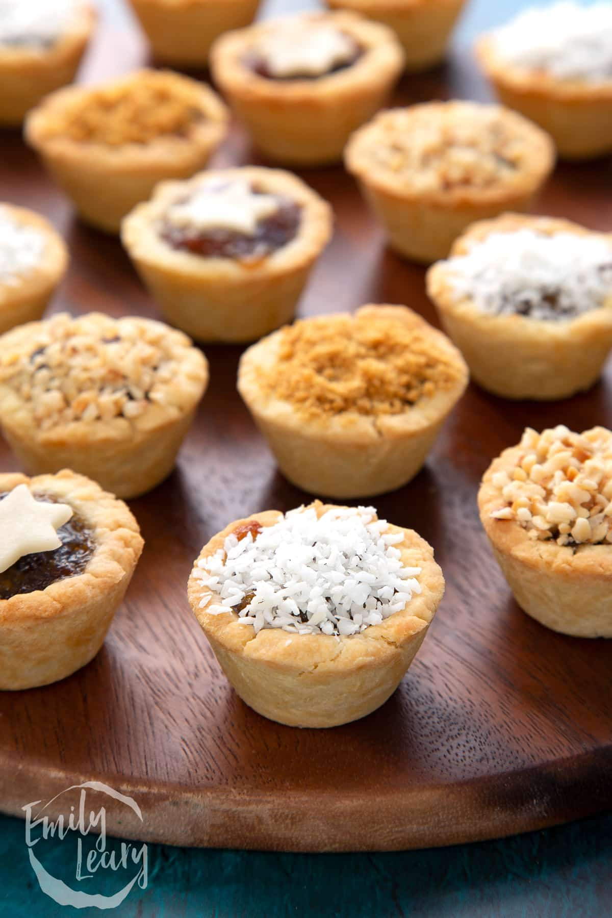 A desiccated coconut topped mini mince pie. More mini mince pies are also on the dark wooden board.