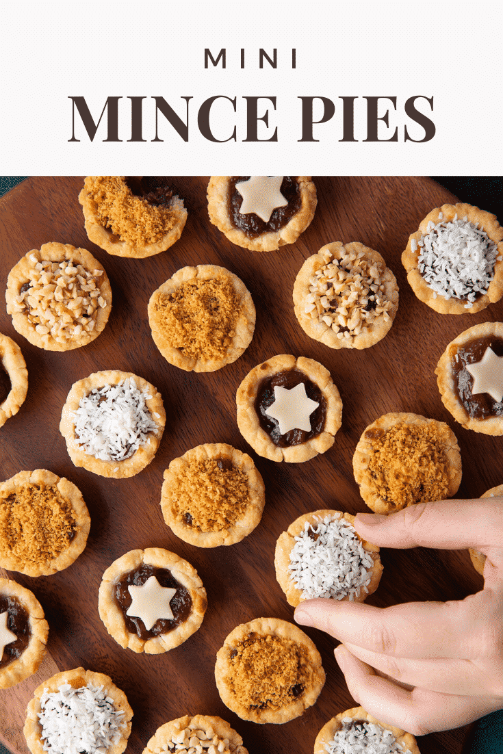 Mini mince pies on a dark wooden board, shown from above. A hand takes one. Caption reads: Mini mince pies.