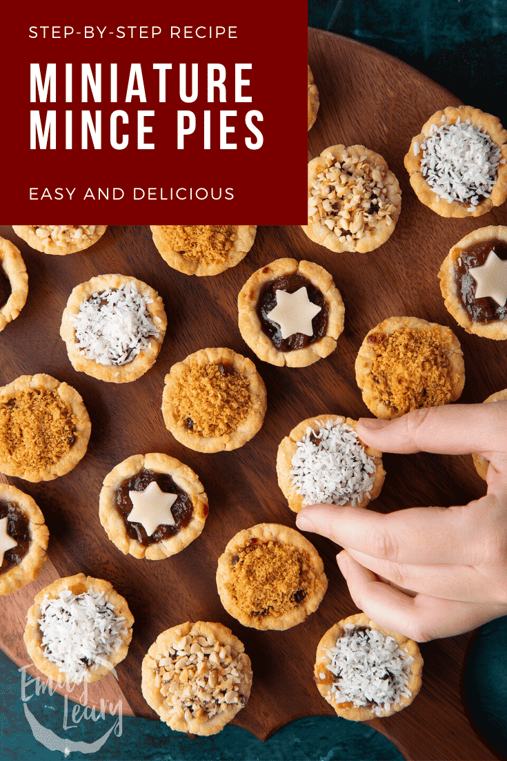 Mini mince pies on a dark wooden board, shown from above. A hand takes one. Caption reads: Step-by-step recipe. Miniature mince pies. Easy and delicious.