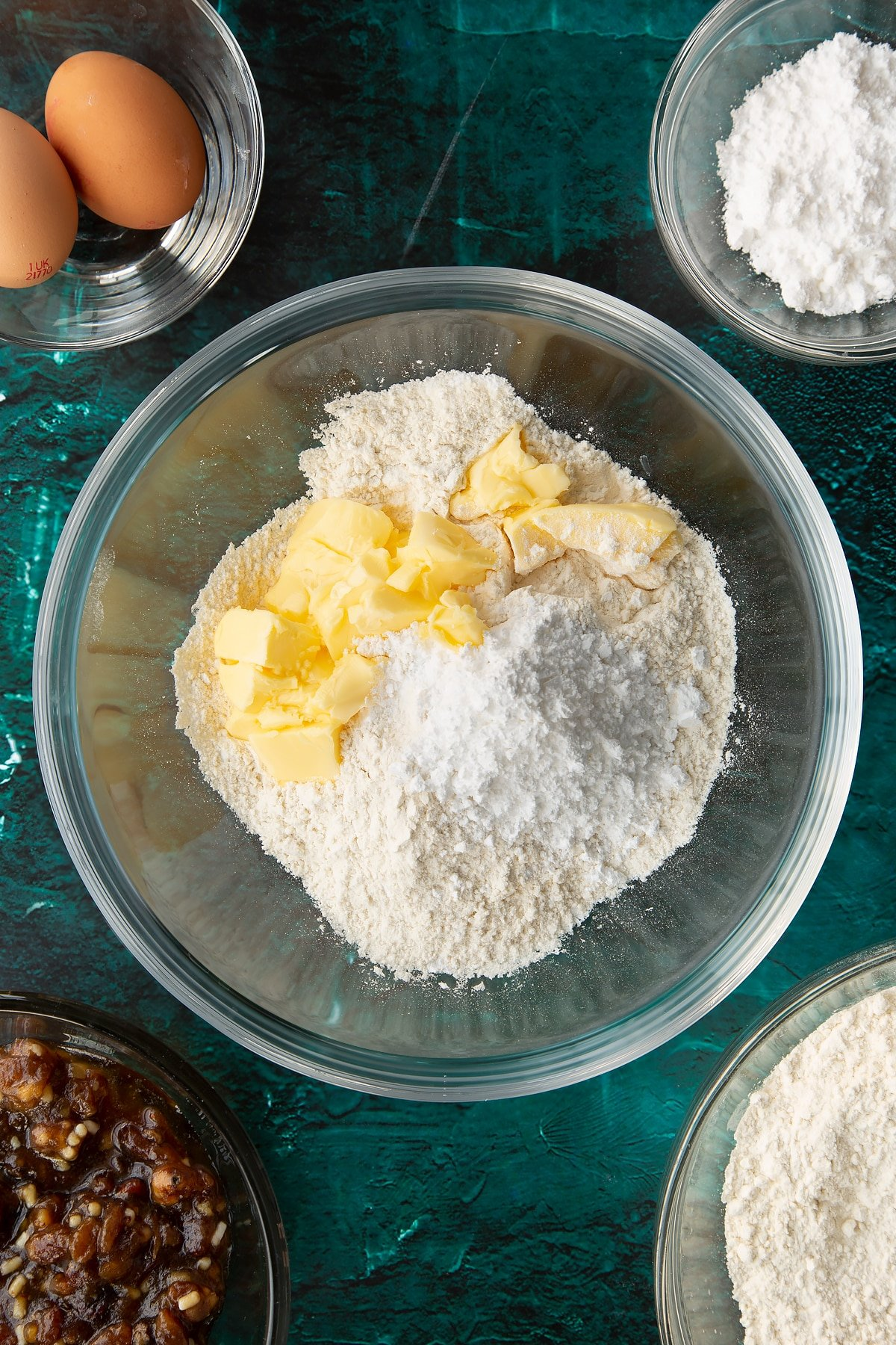 Flour, sugar and butter in a mixing bowl. Ingredients to make mini mince pies surround the bowl.