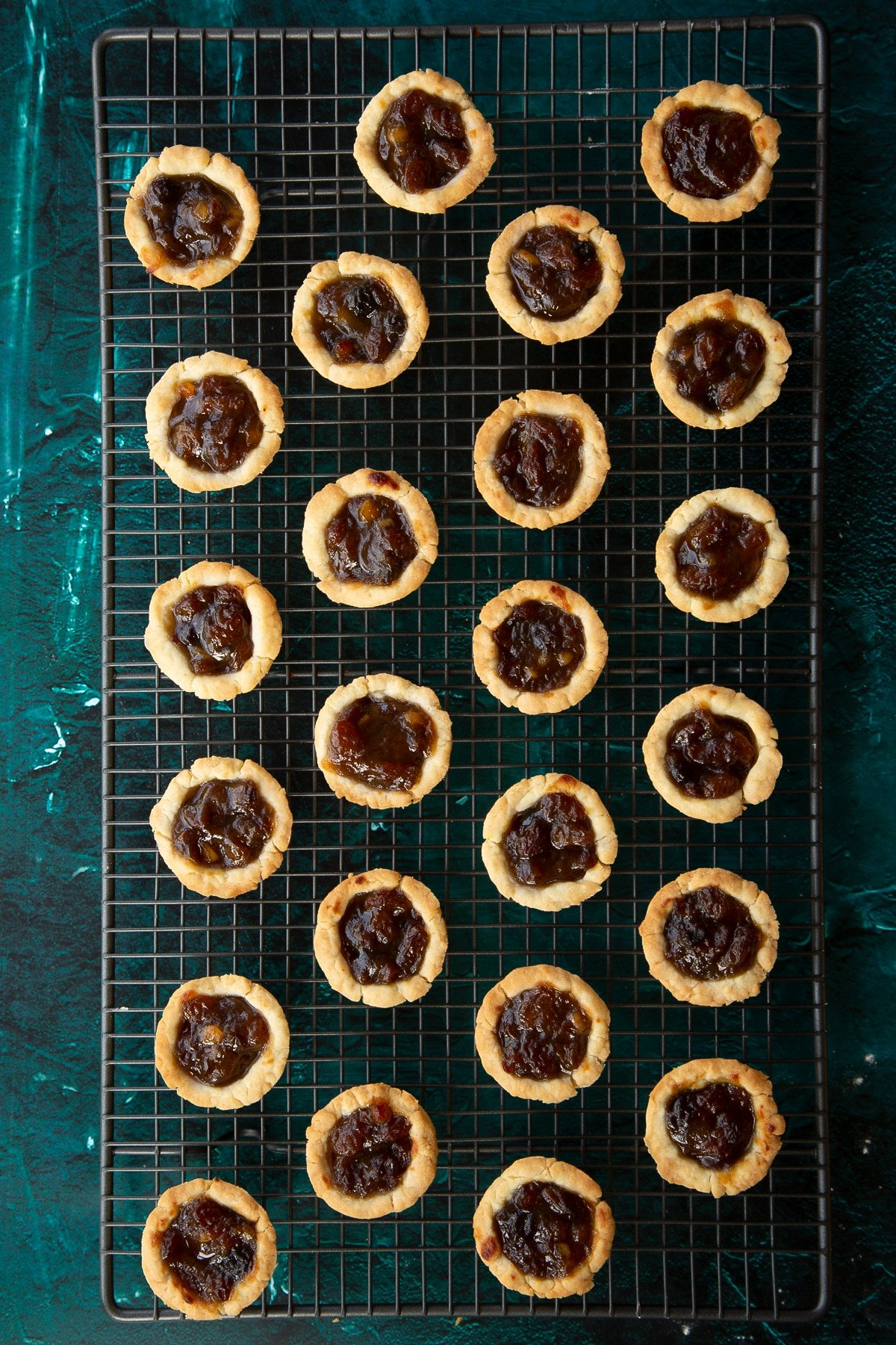 Freshly baked mini mince pies on a cooling rack.