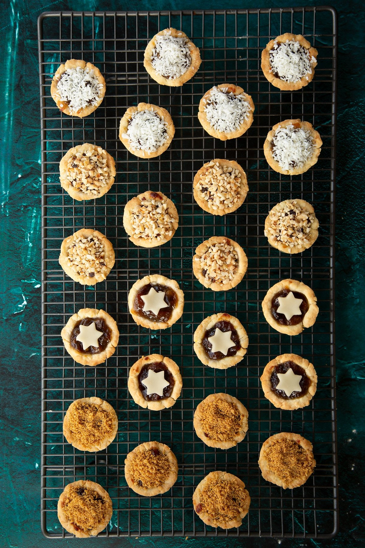 Freshly baked mini mince pies on a cooling rack. They're topped with  marzipan stars, chopped nuts, coconut or crushed gingernuts.