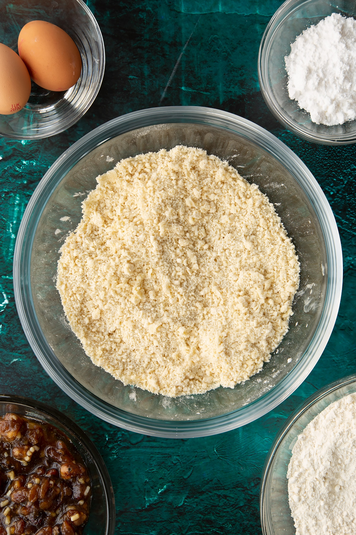 Flour, sugar and butter rubbed together in a mixing bowl. Ingredients to make mini mince pies surround the bowl.