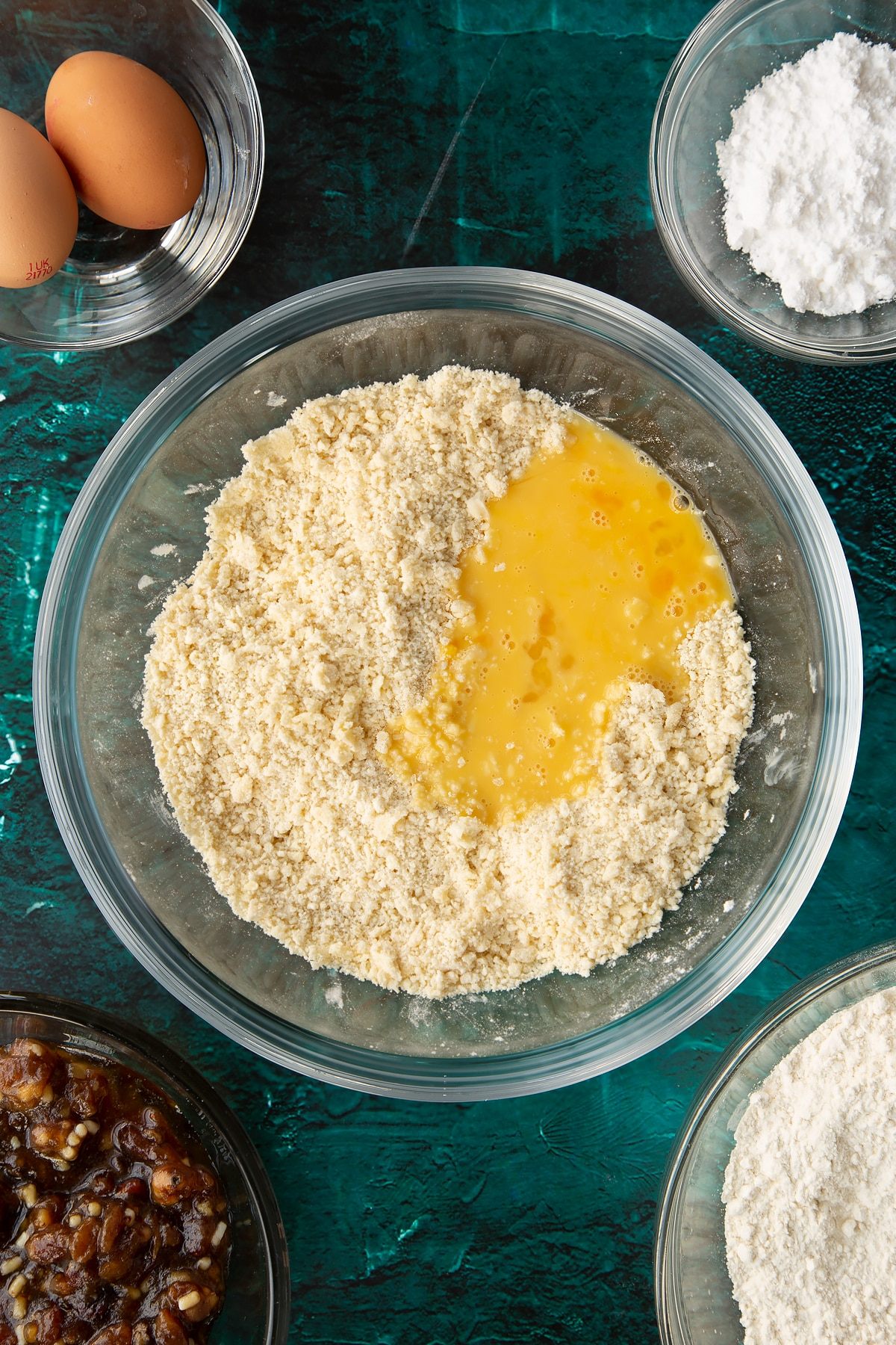 Flour, sugar and butter rubbed together in a mixing bowl with beaten egg on top. Ingredients to make mini mince pies surround the bowl.