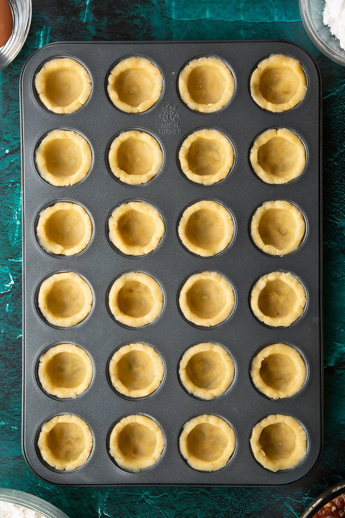 A mini muffin tray with each hole lined with pastry. Ingredients to make mini mince pies surround the tray.