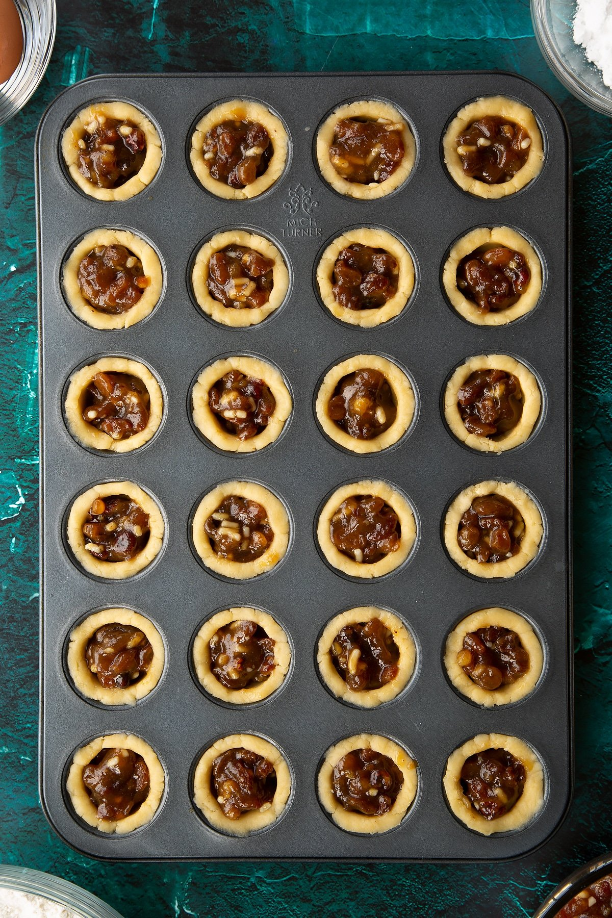 A mini muffin tray with each hole lined with pastry and filled with mincemeat. Ingredients to make mini mince pies surround the tray.
