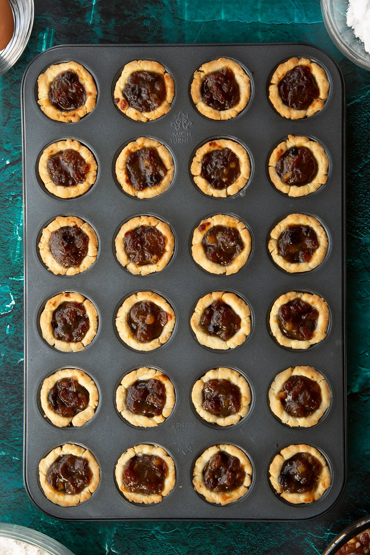 Freshly baked mini mince pies in a mini muffin tray. Ingredients to make mini mince pies surround the tray.