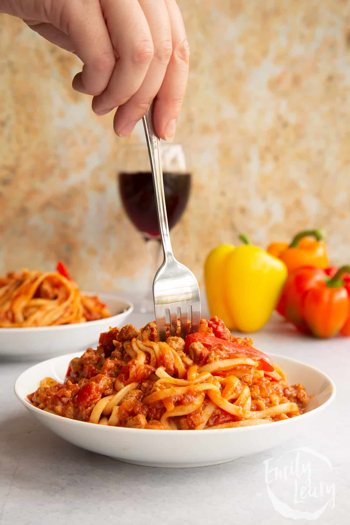One pot vegan bolognese in a shallow white bowl. A hand holds a fork delving into the bowl.