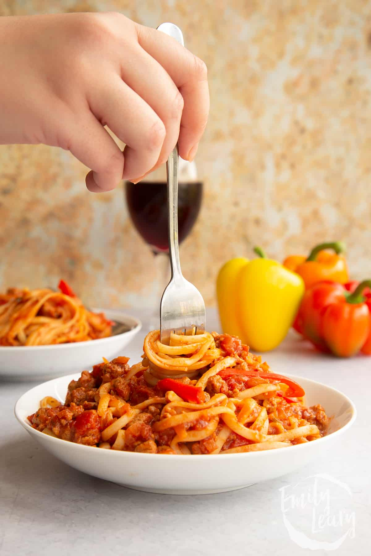 One pot vegan bolognese in a shallow white bowl. A hand holds a fork, twisting spaghetti in the bowl.