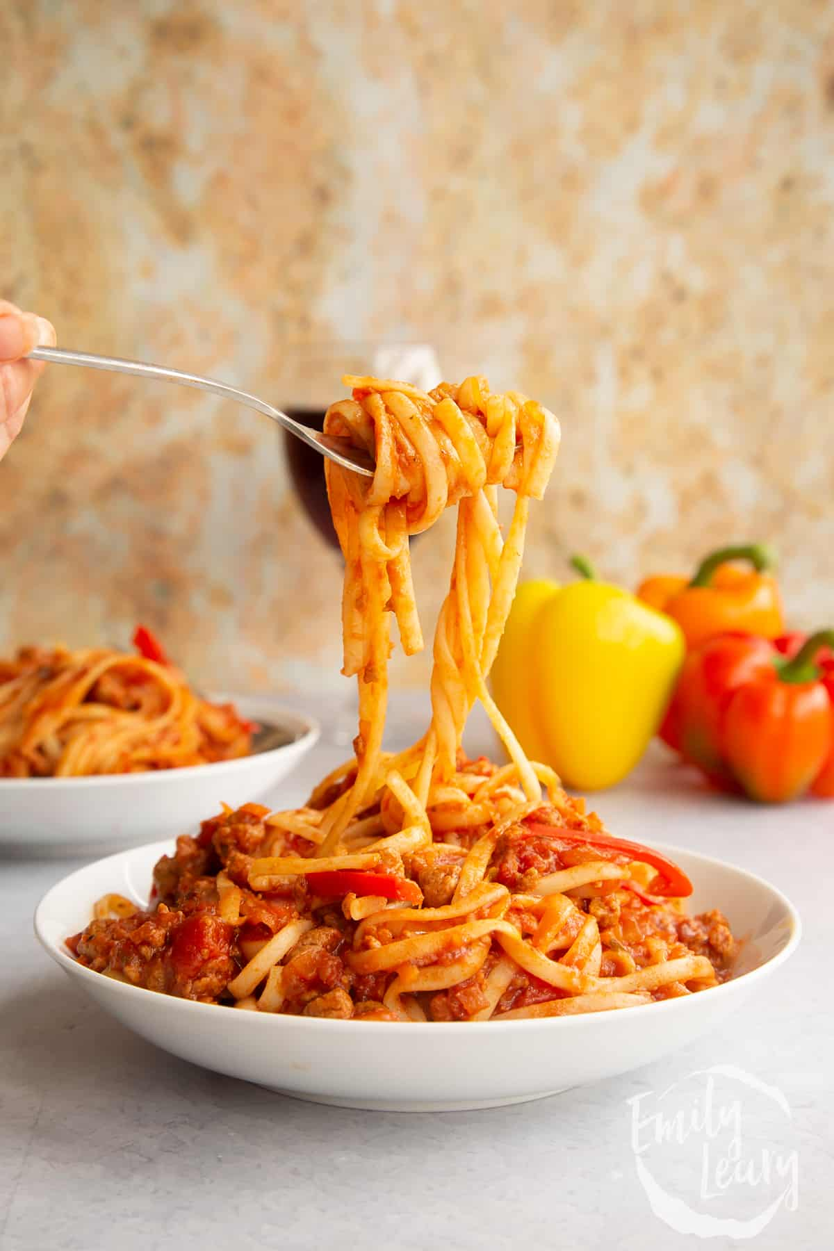 One pot vegan bolognese in a shallow white bowl. A hand lifts spaghetti from the bowl.