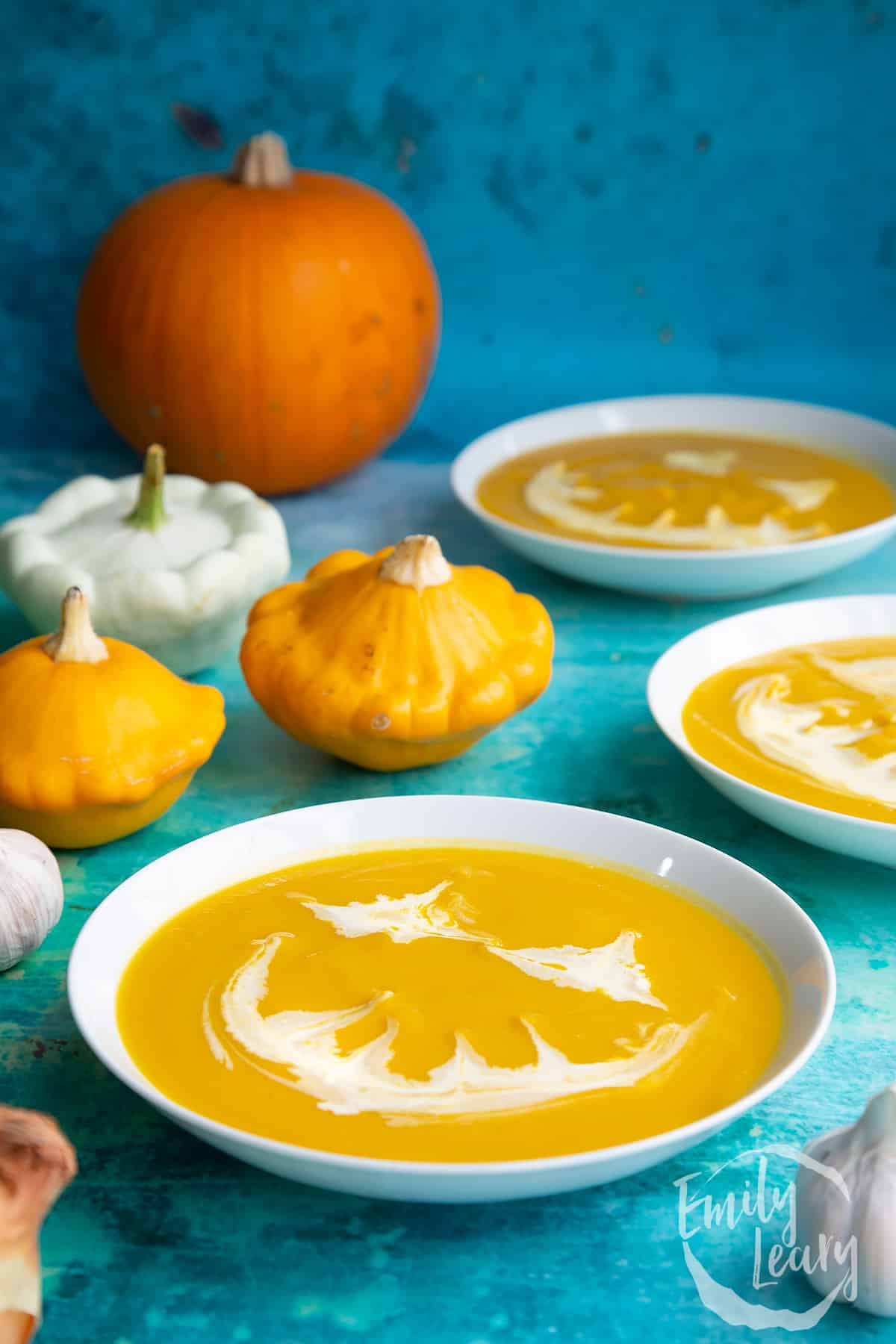 Pumpkin and sweet potato soup in a white bowl. The soup has cream swirled on top to resemble a jack'o'lantern.