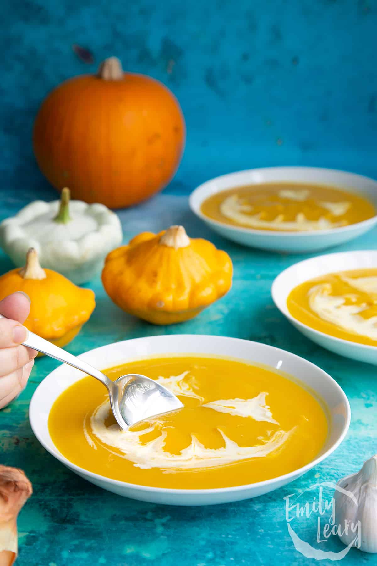 Pumpkin and sweet potato soup in a white bowl. The soup has cream swirled on top to resemble a jack'o'lantern. A hand holds a spoon, dipping into the soup.