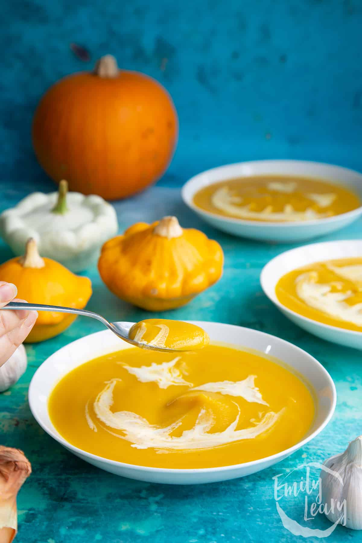 Pumpkin and sweet potato soup in a white bowl. The soup has cream swirled on top to resemble a jack'o'lantern. A spoon lifts some of the soup.