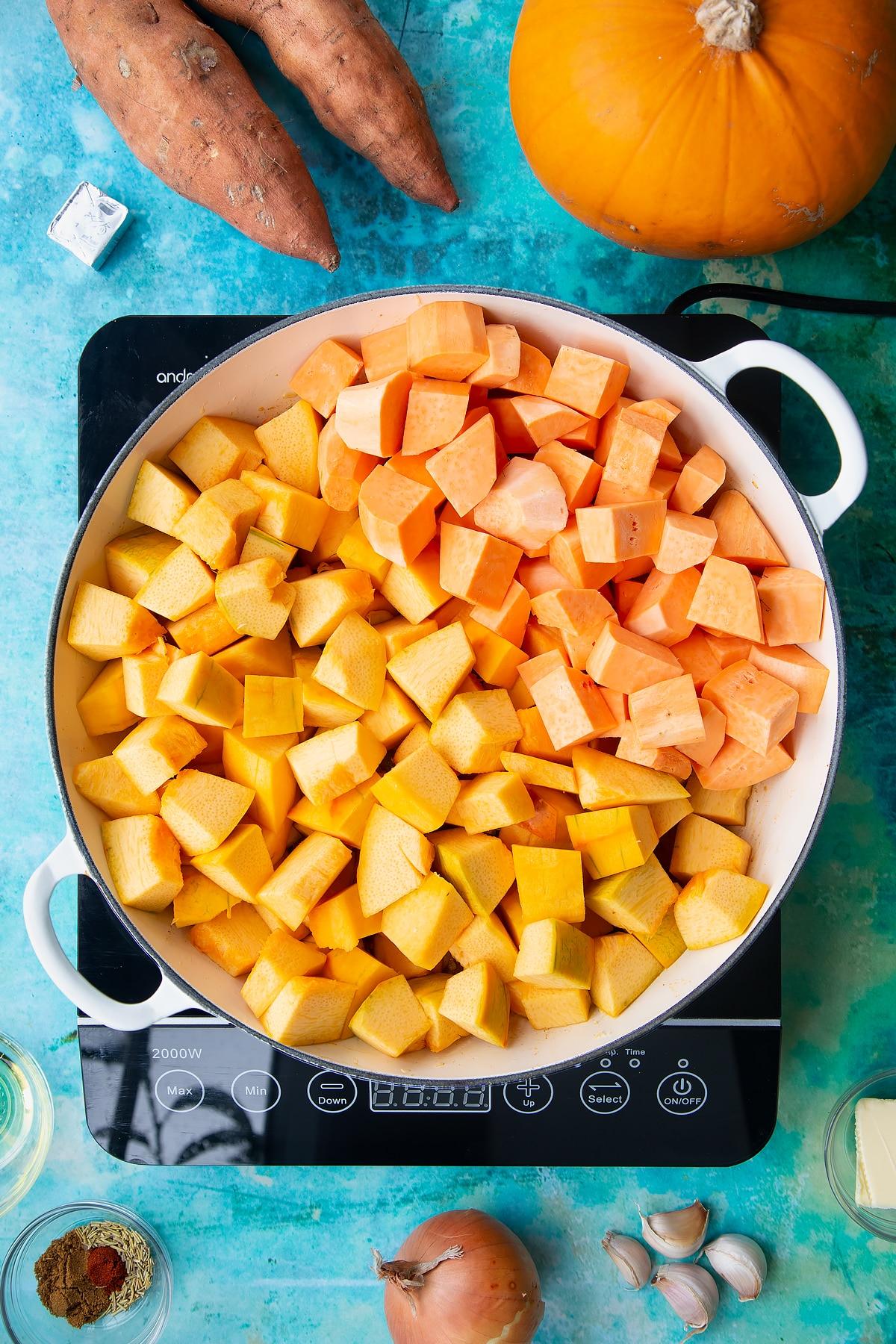Chopped pumpkin and sweet potato on top of sweated onion and garlic in a large, shallow pan, from above. Ingredients to make pumpkin and sweet potato soup surround the pan.