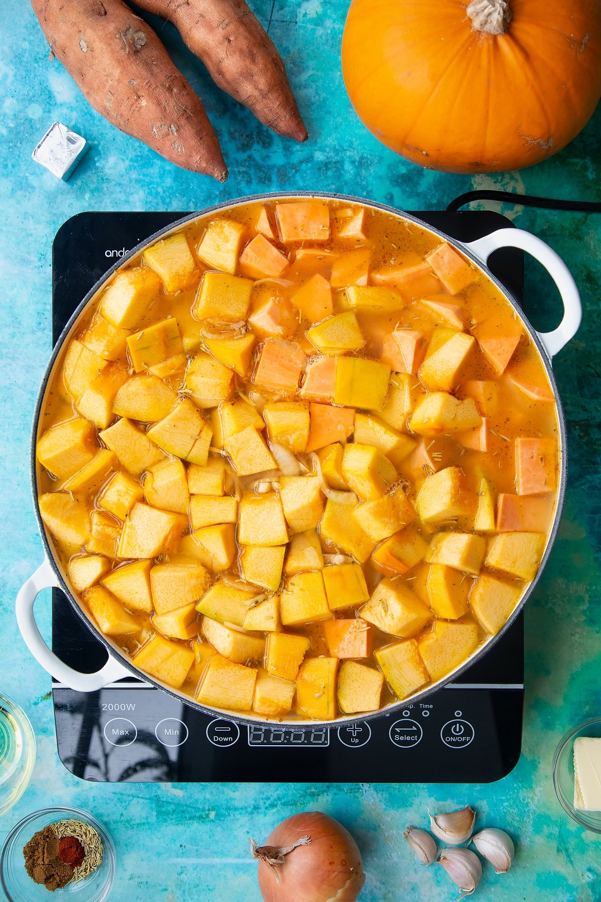 Pumpkin, sweet potato, onion, garlic and stock in a large, shallow pan, from above. Ingredients to make pumpkin and sweet potato soup surround the pan.