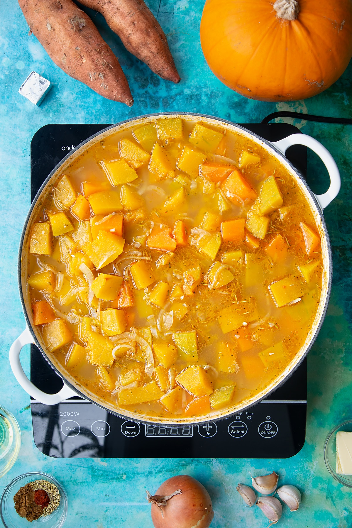 Pumpkin, sweet potato, onion and garlic cooked in stock in a large, shallow pan, from above. Ingredients to make pumpkin and sweet potato soup surround the pan.