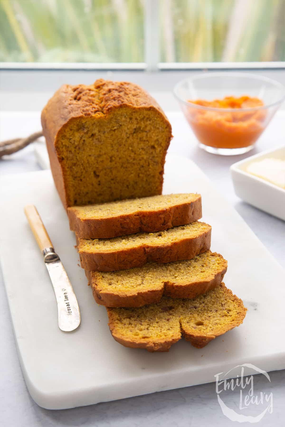 A pumpkin banana bread loaf on a white marble board. Some has been sliced.