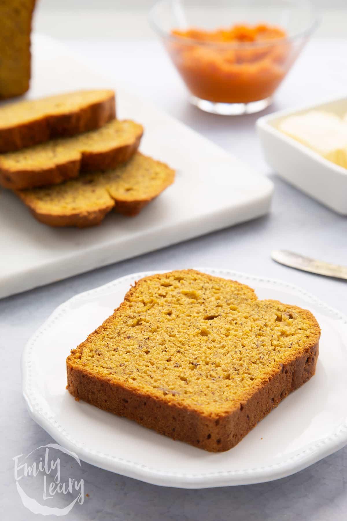 Slice of pumpkin banana bread on a white plate.