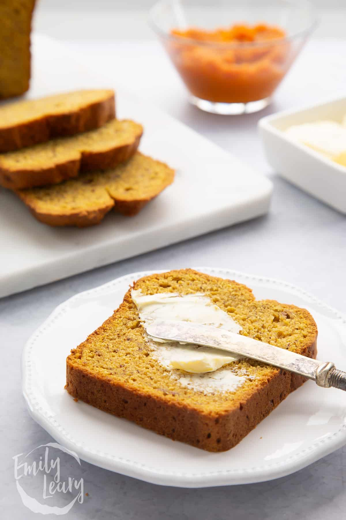 A slice of pumpkin banana bread on a small white plate. It is being buttered with a small knife.
