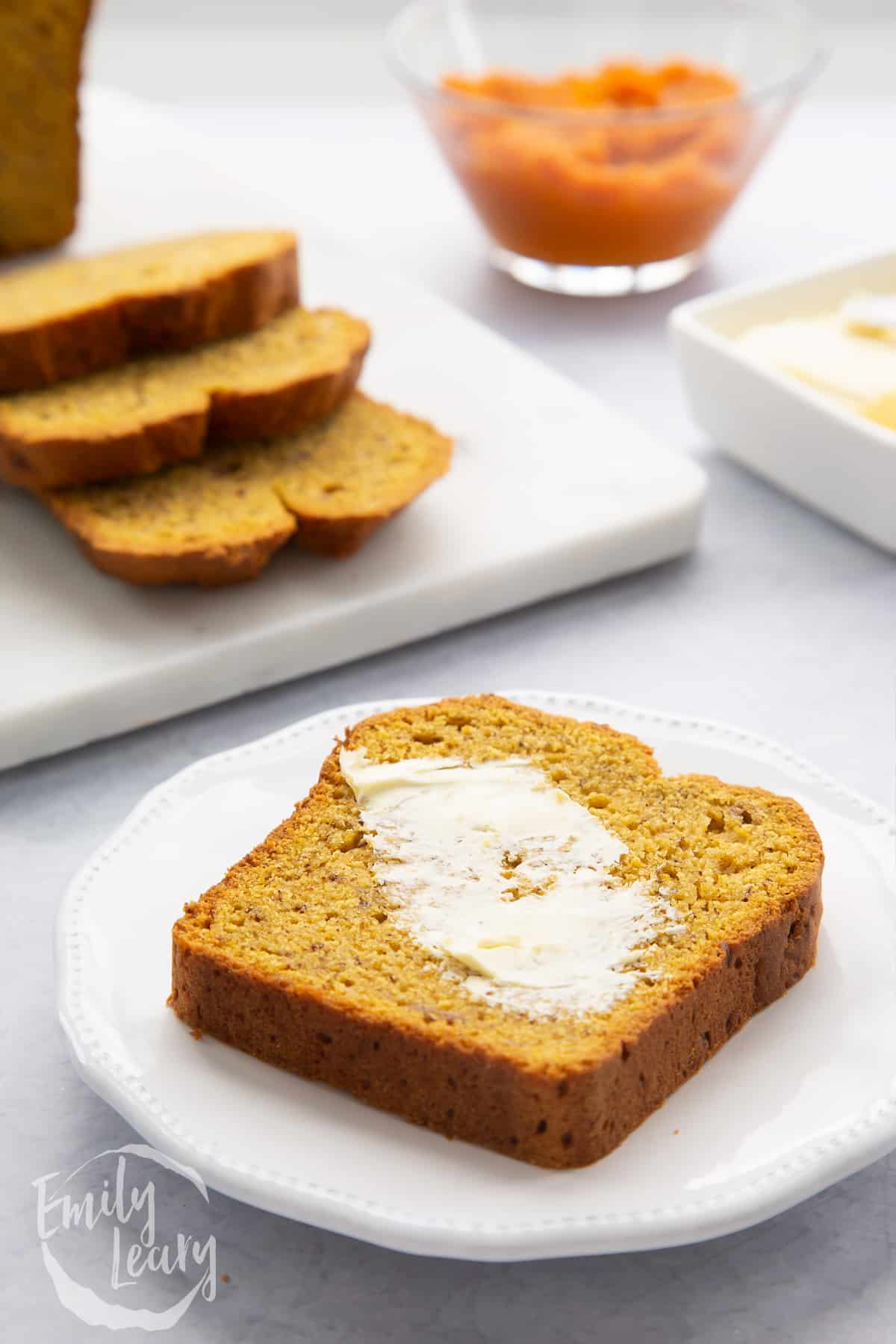 A buttered slice of pumpkin banana bread on a white plate.