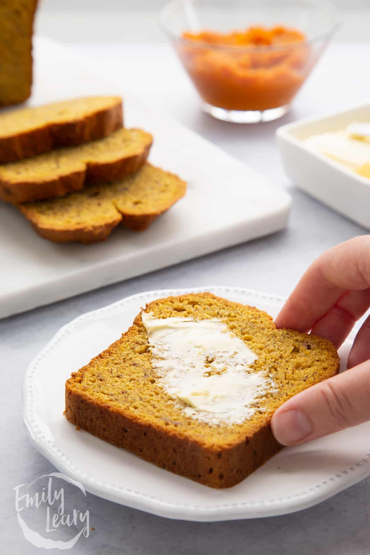 A buttered slice of pumpkin banana bread on a white plate. A hand reaches to take it.