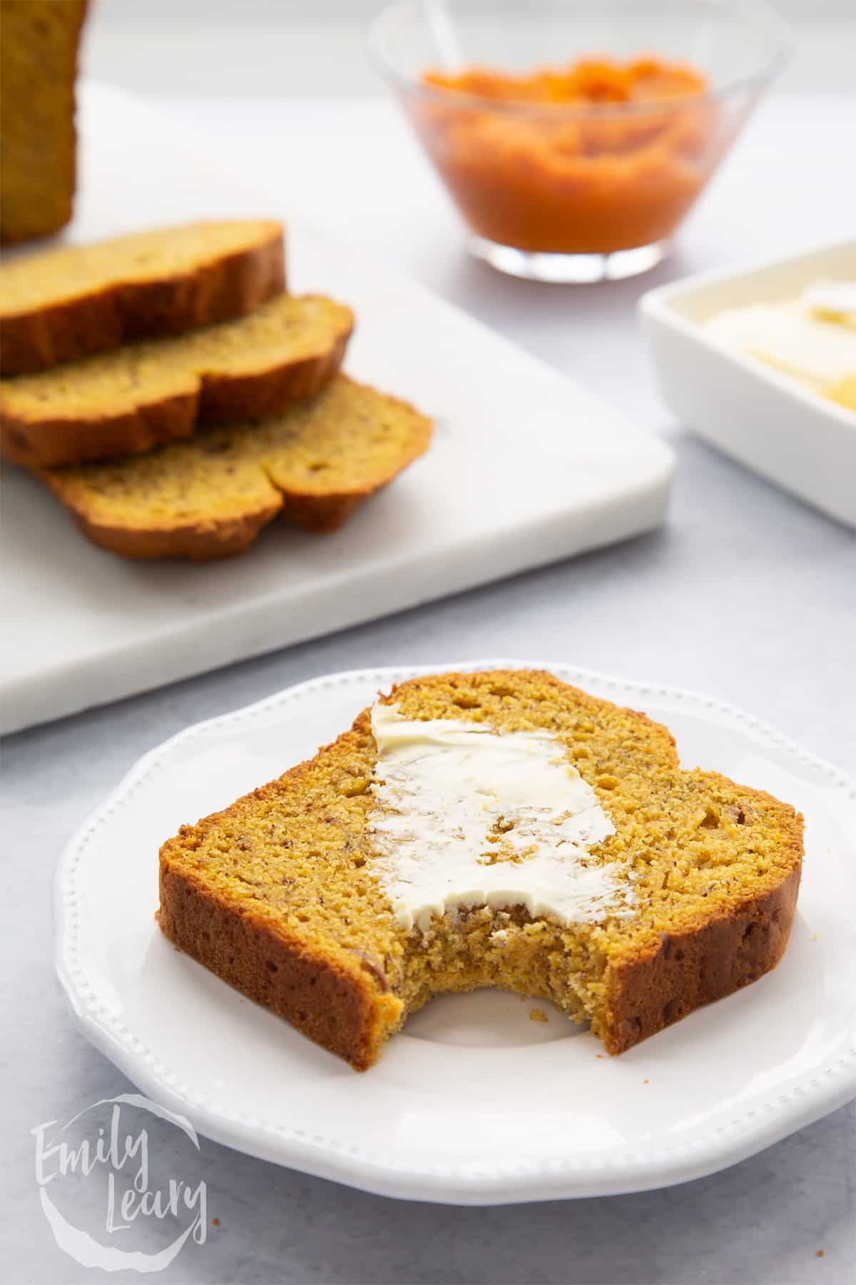A buttered slice of pumpkin banana bread on a white plate with a bite out of it.