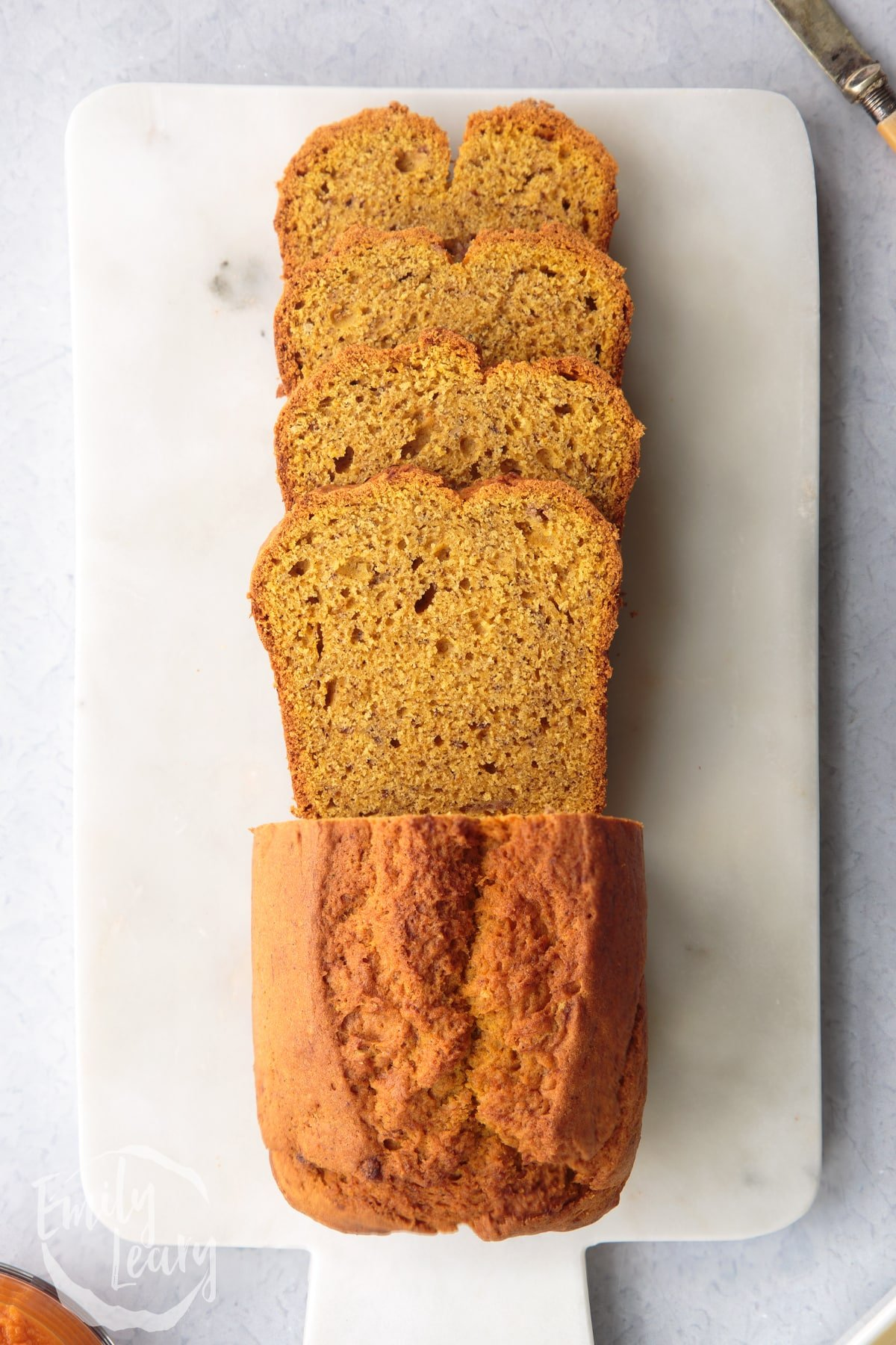 Pumpkin banana bread loaf on a white marble board. Some has been sliced.