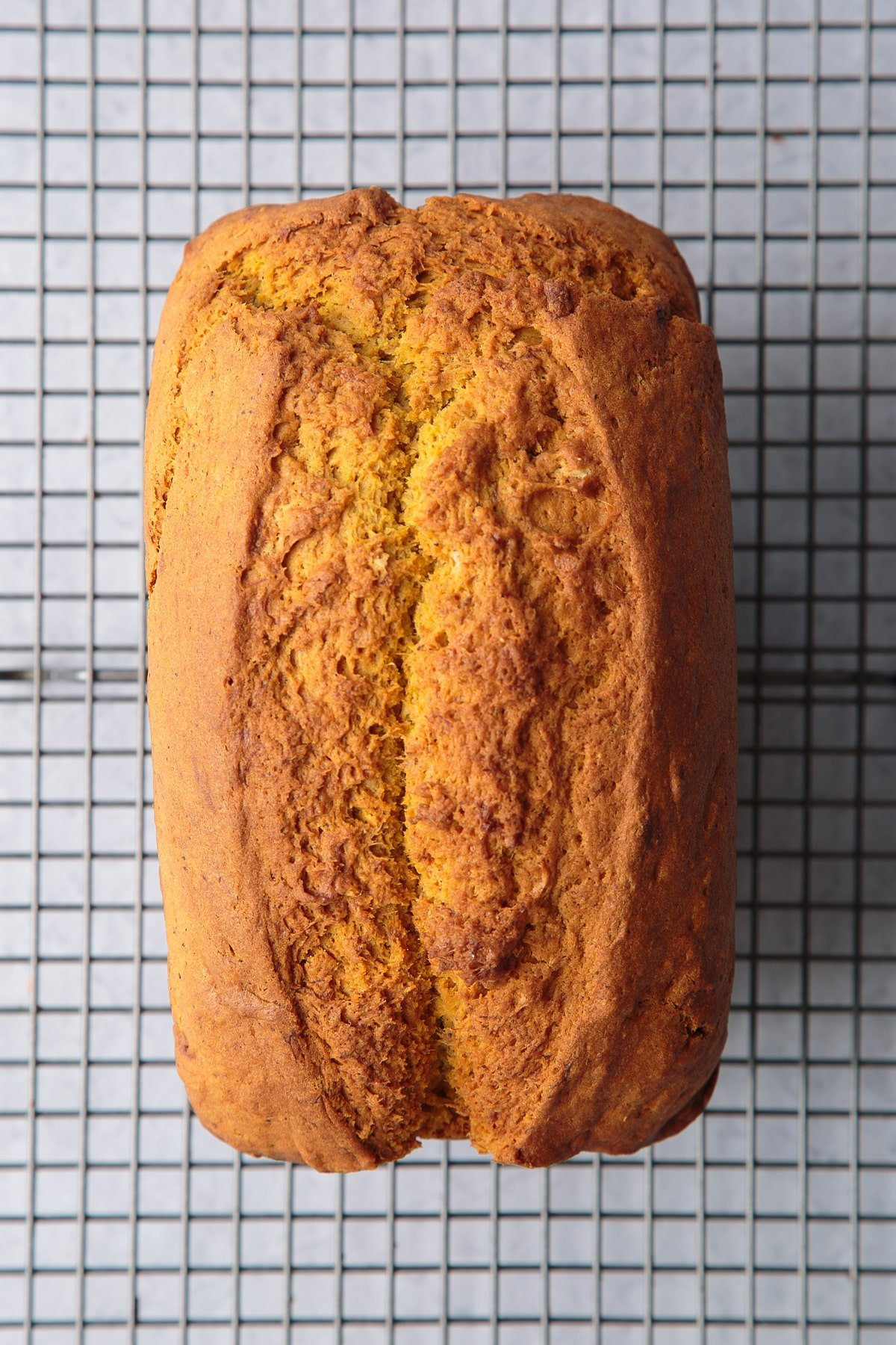 Pumpkin banana bread loaf cooling on a wire rack.