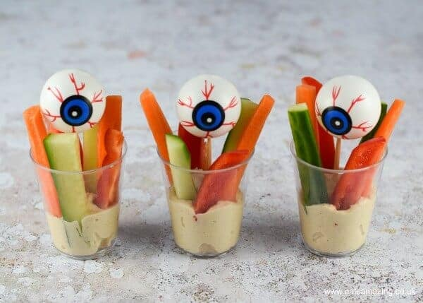 Hummus at the bottom of three plastic cups, topped with fingers of raw carrot, pepper and cucumber. Decorative plastic eyeballs have been added to each cup.