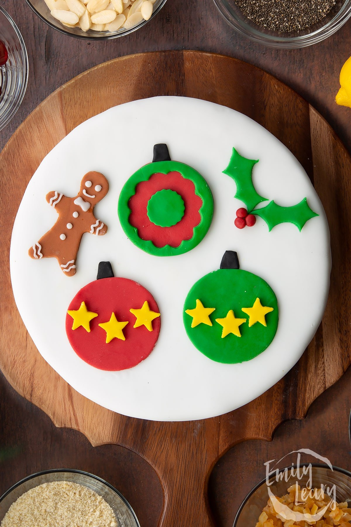 Vegan Christmas cake, topped with a disc of marzipan, covered with white sugar paste and decorated with sugar paste decorations (three baubles, a sprig of holly and a little gingerbread man).