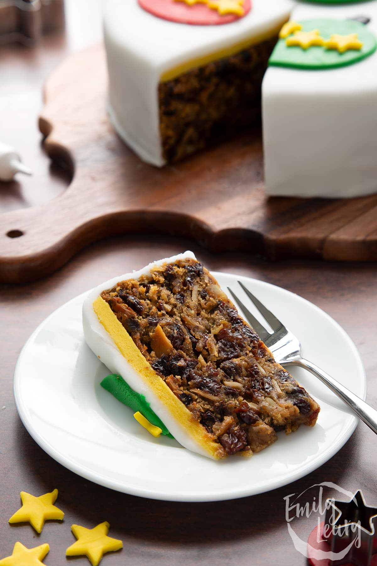 Slice of vegan Christmas cake on a white plate with a fork.