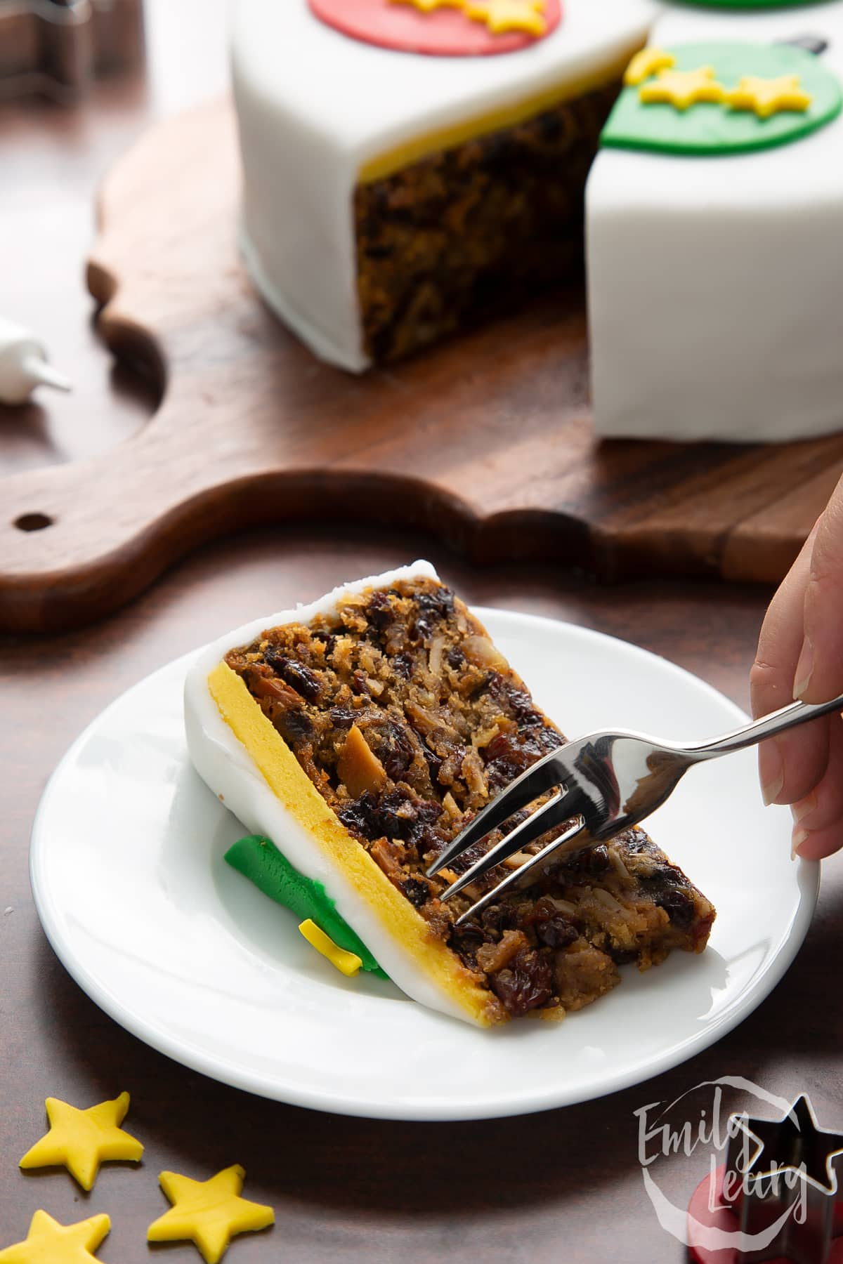 Slice of vegan Christmas cake on a white plate. A hand holds a fork.