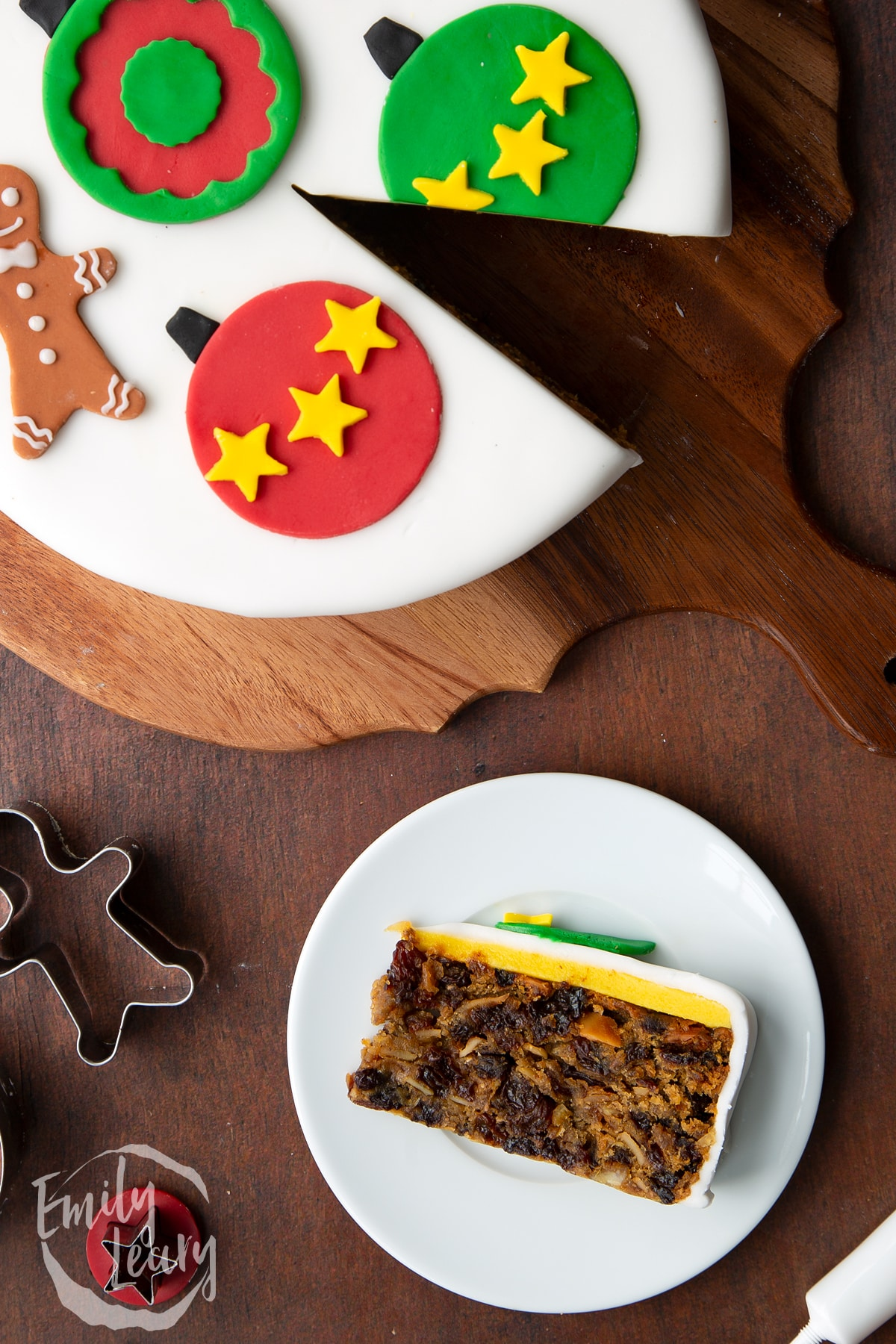Slice of vegan Christmas cake laying on its side on a white plate. Shown from above.