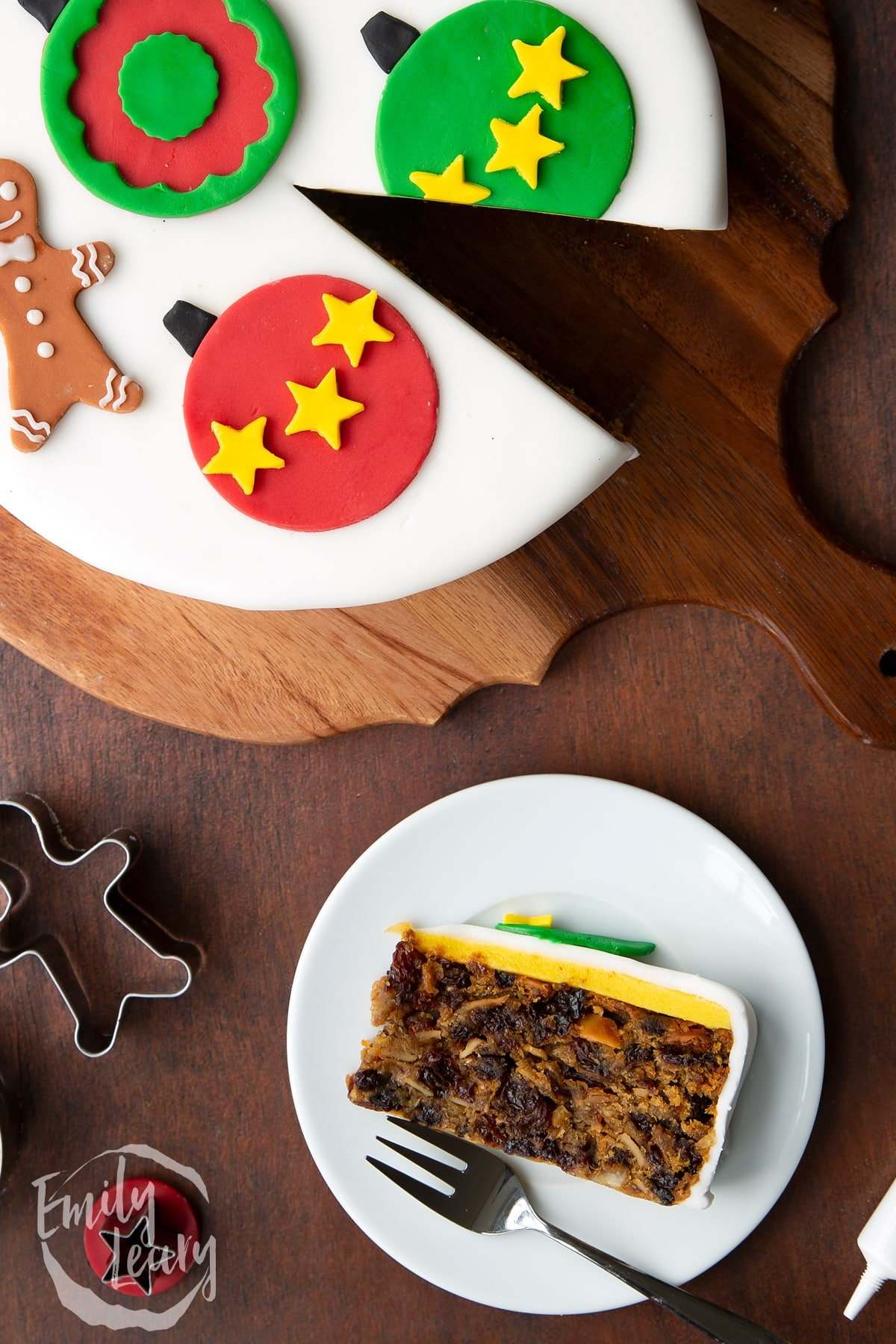 Slice of vegan Christmas cake laying on its side on a white plate with a fork. Shown from above.