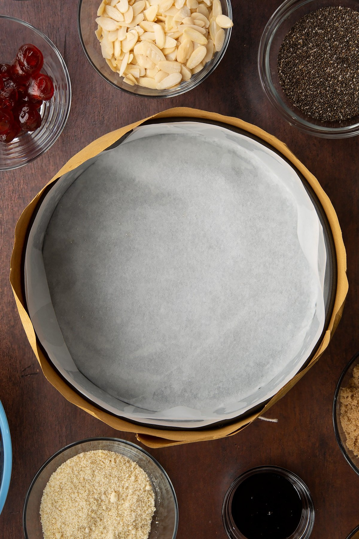 Cake tin lined with baking paper and wrapped in brown paper, tied with string. Ingredients to make vegan Christmas cake surround the tin.