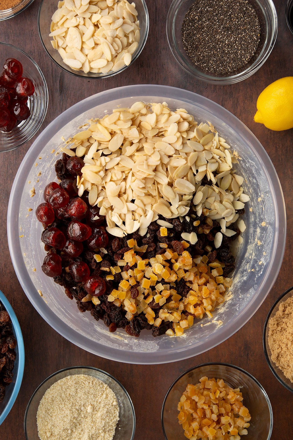 Butter, sugar, treacle, flour, almonds, spices, citrus juice and plant milk in a bowl with flaked almonds, cherries and mixed peel on top. Ingredients to make vegan Christmas cake surround the bowl.